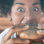 une jeune femme noire croque dans un burger vegan