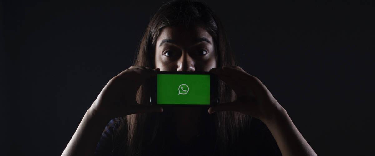 Une femme tient son smartphone devant sa bouche. Sur l'écran, la plateforme WhatsApp