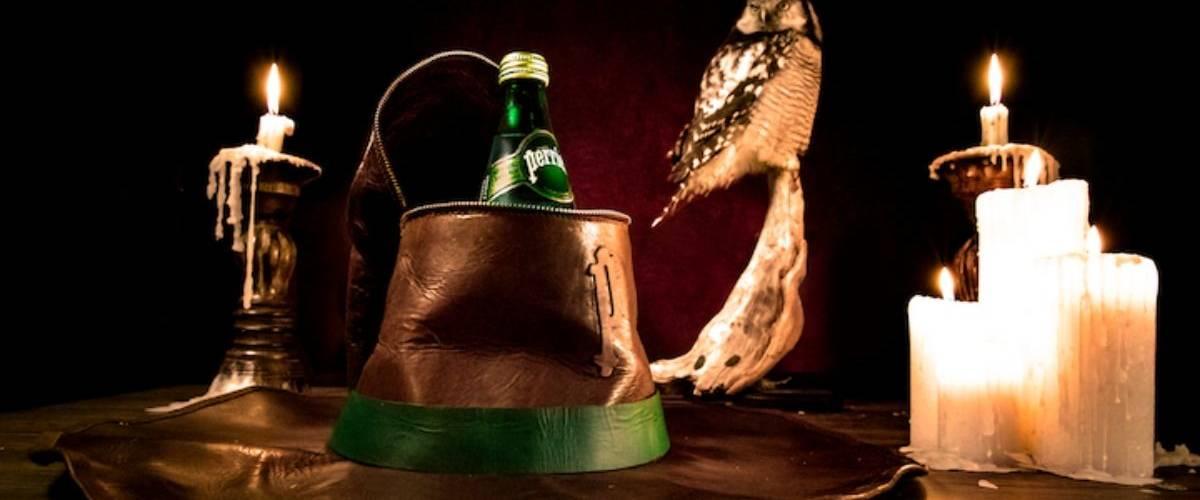 Un chapeau de sorcier contient une bouteille eau gazeuse Perrier au frais