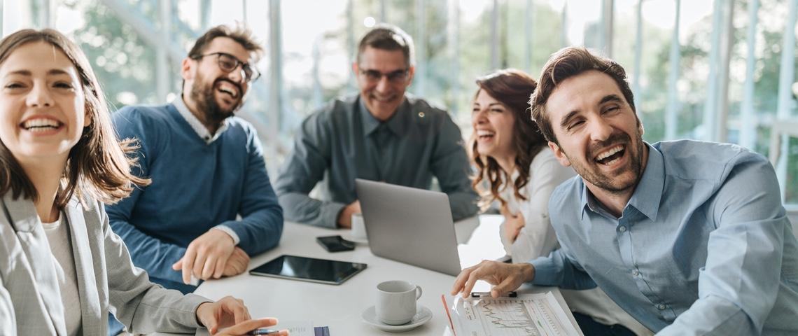 Groupe de salariés hilares autour d'une table de réunion