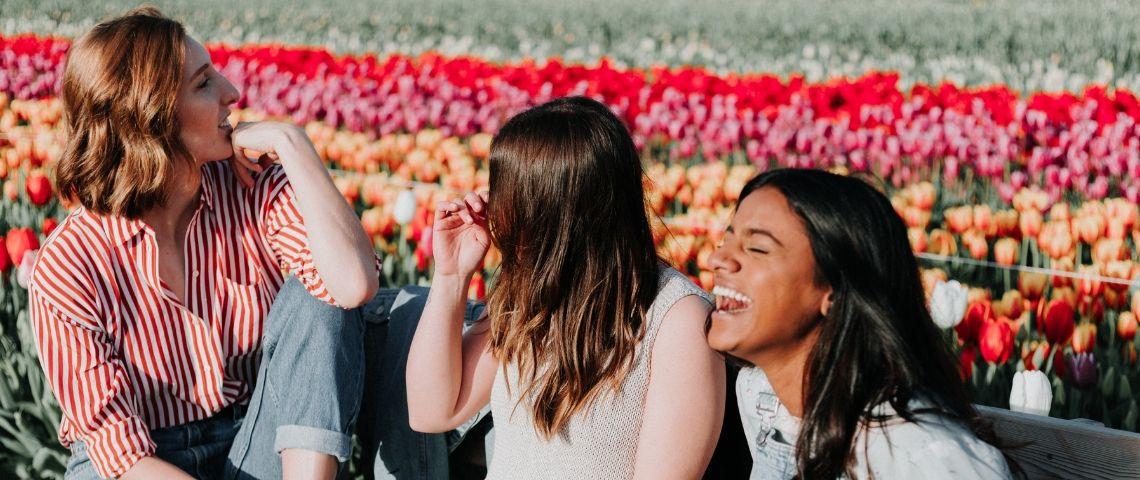 trois filles qui rient devant des fleurs