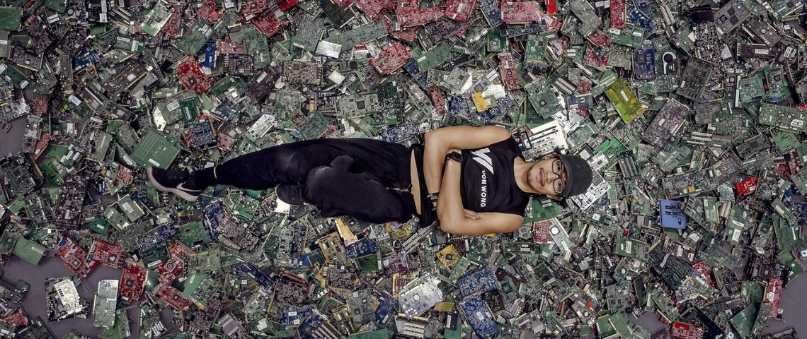 un homme allongé sur des déchets électroniques