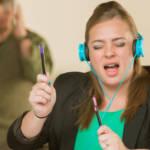 Une jeune femme en train d'écouter de la musique bruyamment à son bureau et un homme énervé en arrière-plan