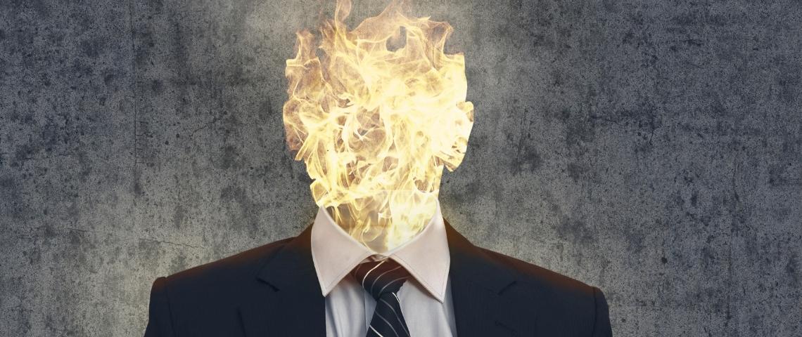 Un homme en costume dont la tête est enflammée