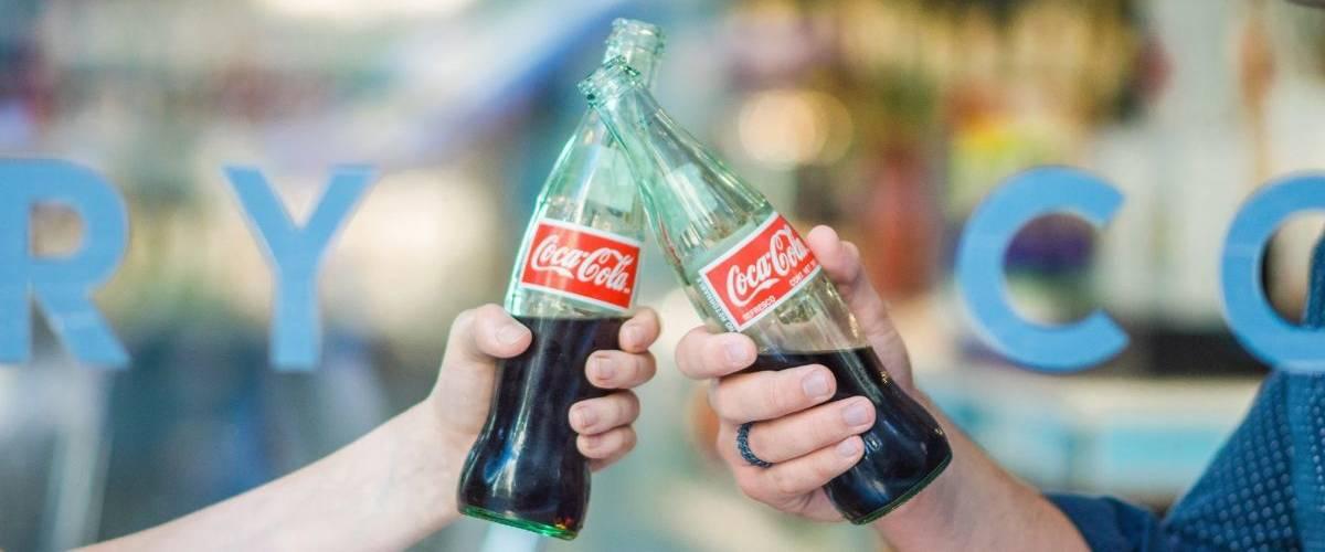Deux mains trinquent avec des bouteilles Coca-Cola