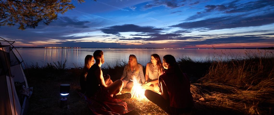 Un groupe de jeunes gens autours d'un feu le soir