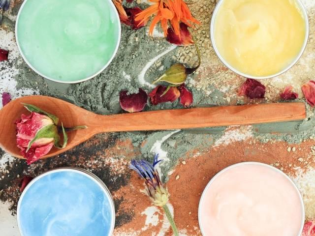 Plan de travail de cosmétique fait-main. Cuillère en bois avec une fleur, quatre pots de masques colorés faits-main autour