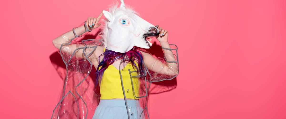 Une femme avec une tete de licorne sur un fond rose