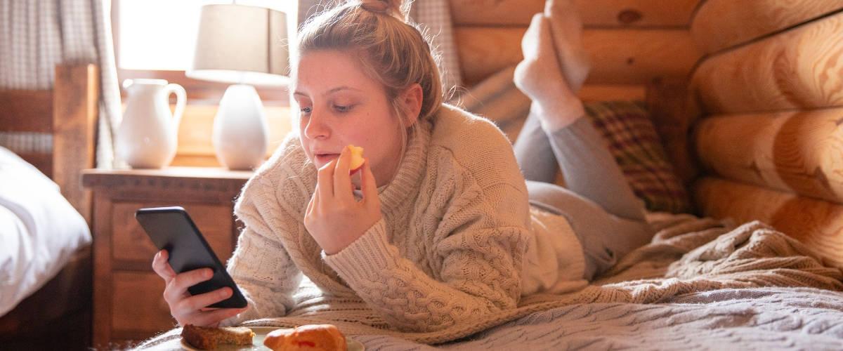 Une fille blonde qui mange allongée sur son lit en regardant son téléphone