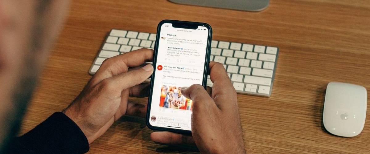Une homme regarde une page du réseau social Twitter sur son téléphone