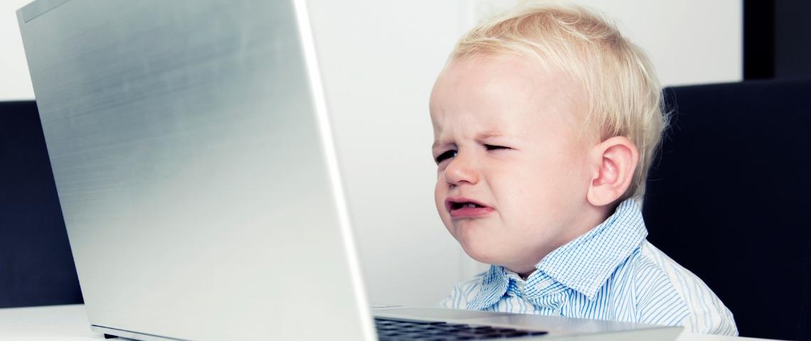 un enfant grincheux devant un ordinateur