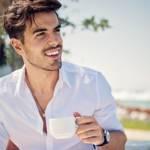 Un homme boit un café en bord de mer