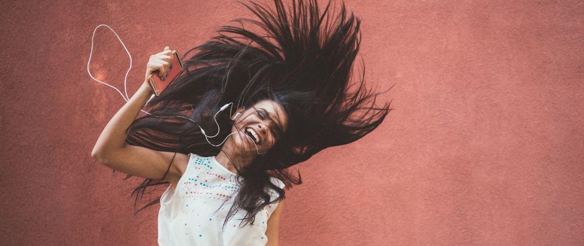 Une femme aux longs cheveux sourit en écoutant la musique