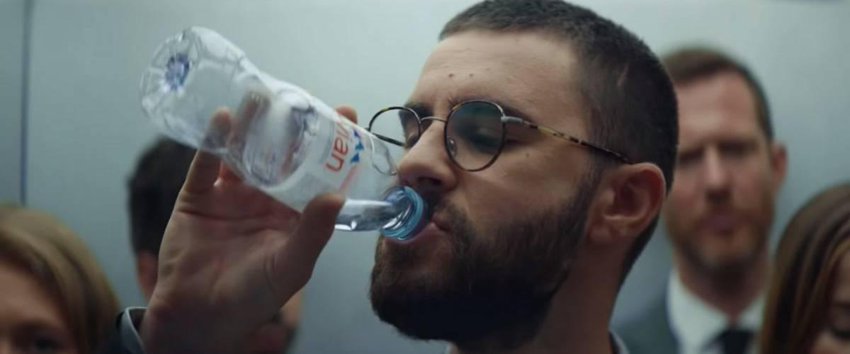Le youtubeurs Cyprien boit une bouteille d'eau evian dans un ascenseur