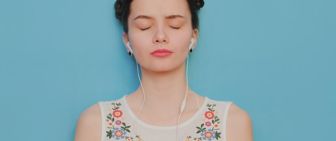 une femme sur fond bleu écoute de la musique