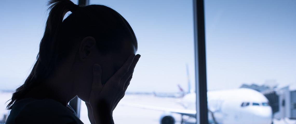 Silhouette d'une femme se cachant les yeux avec les mains, derrière elle un avion sur le tarmac.