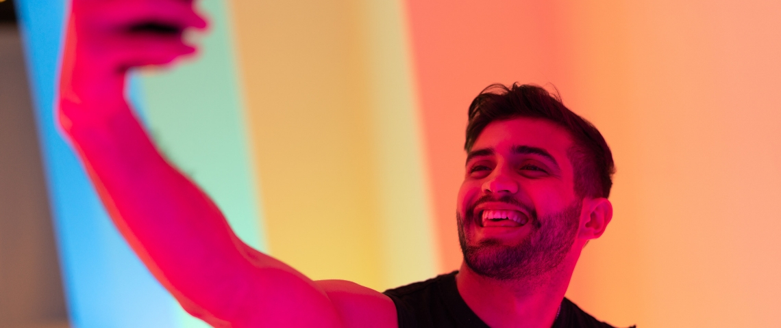 une jeune homme se prend en selfie avec de la lumière rose