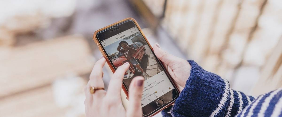 Une femme regarde son film d'actualité Instagram sur son smartphone