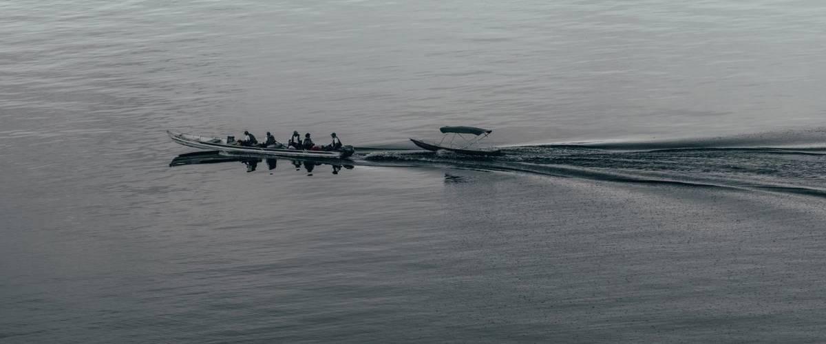 Un long bateau longe un lac exotique