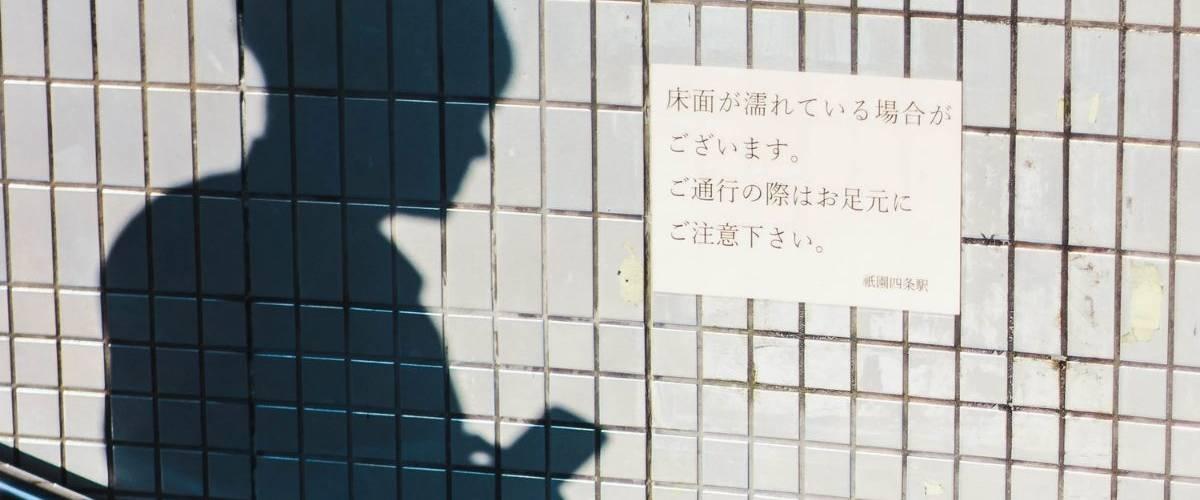 Ombre d'un homme tenant son téléphone, sur le coté une affiche japonaise