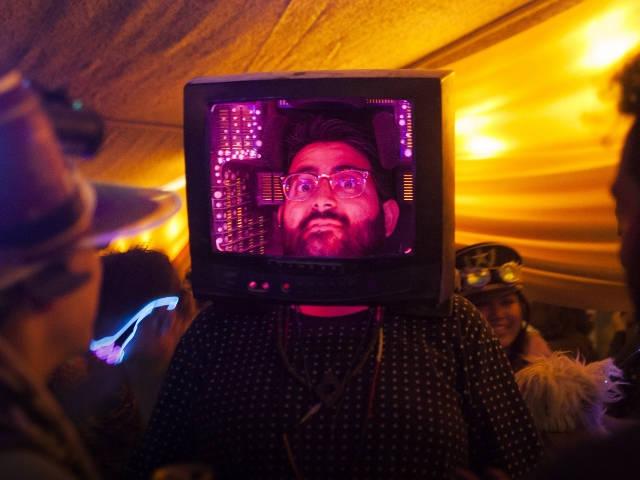un homme qui la tête dans une vieille télévision rose.