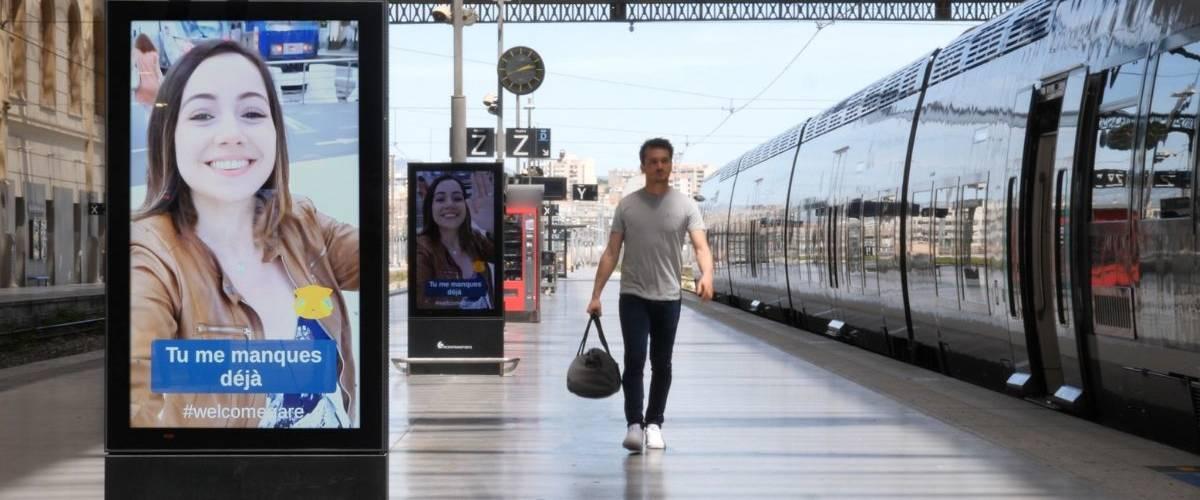 Un homme regarde sa petite amie qui lui laisse un message sur les panneaux digitaux d'une gare