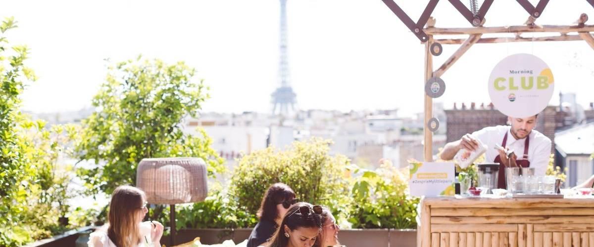 Un groupe de femme face à un bar à jus de fruit Zespri, sur les toits de Paris