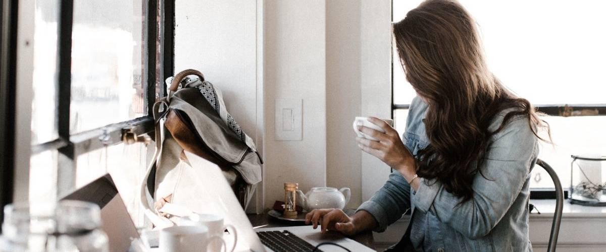 Une femme brune, porte une veste en jean. Elle se tient devant son bureau , sur son ordinateur et bois un café