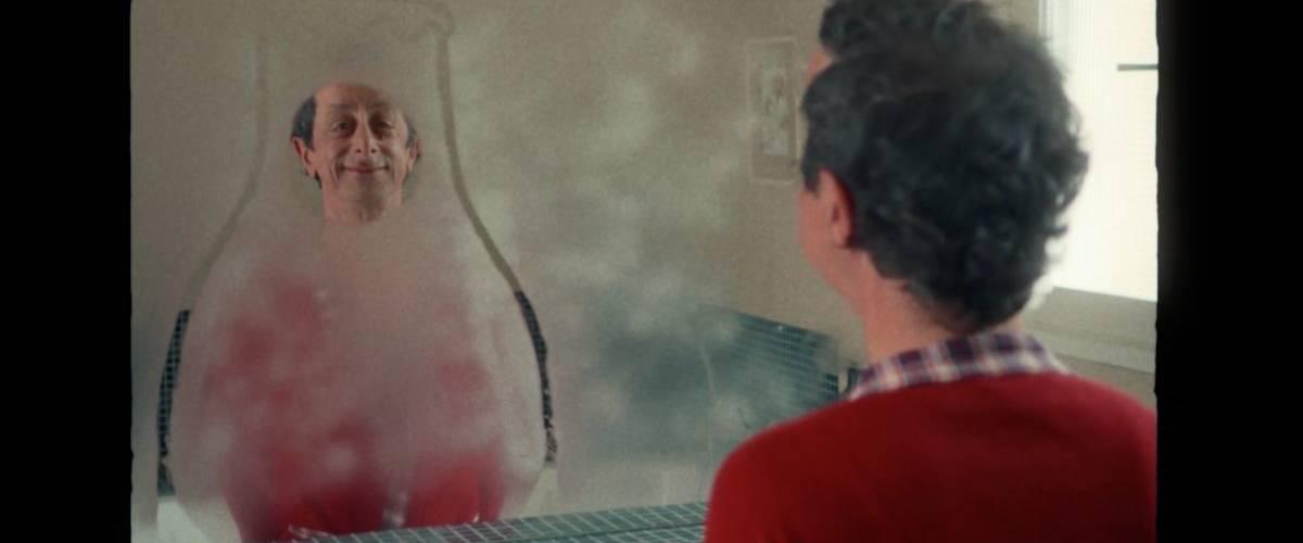 Un homme se tient devant son miroir