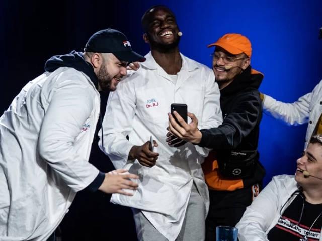 un groupe de jeunes homme en blouse blanche qui regarde un téléphone portable en rigolant