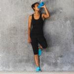 Une femme en tenue de sport qui boit dans une bouteille bleue
