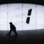 Homme se déplaçant devant un écran géant