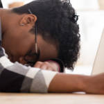 une femme en train de dormir devant son ordinateur
