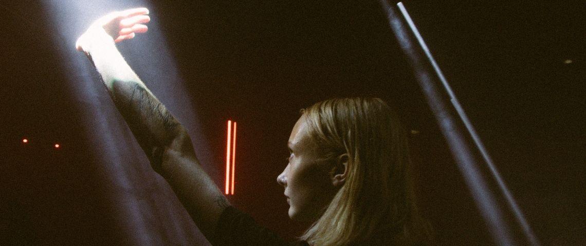une jeune femme tatouée coupe la lumière avec sa main