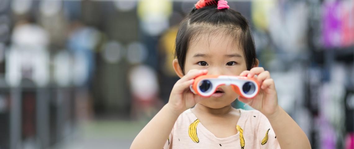 Une petite fille chinoise qui tient des jumelles dans les mains