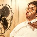 Un employé de bureau en train de se rafraîchir avec un ventilateur