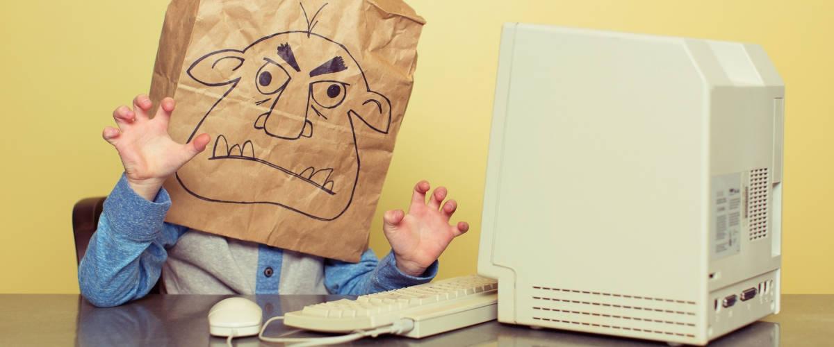Un enfant devant un ordinateur avec un sac sur la tête