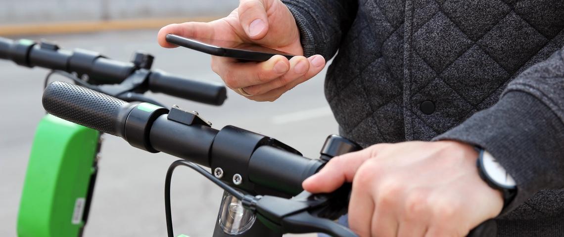 Un homme paye une trottinette électrique avec son smartphone.