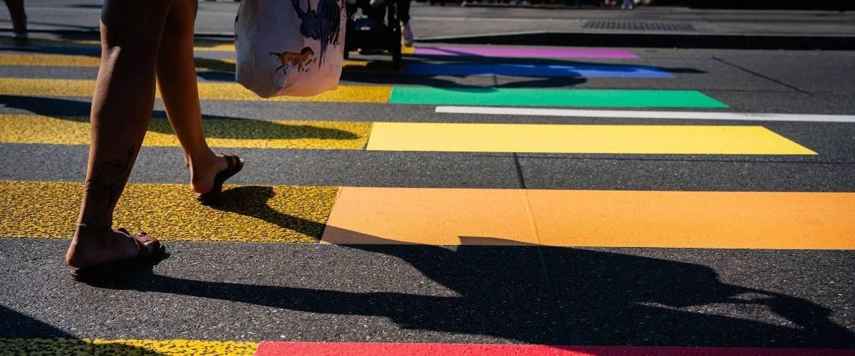 Une femme passe sur un passage piéton aux couleurs du drapeau de la communauté LGBT+