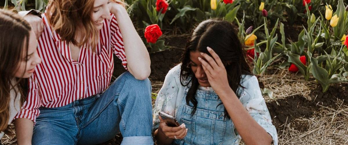 Trois jeunes femmes se prennent en photo sur un smartphone. Au milieu d'un champ de tulipes.