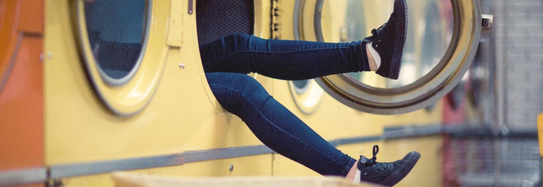 Des jambes qui sortent d'une machine à laver dans une laverie