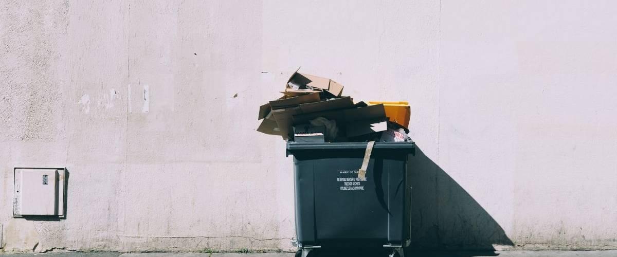 Une benne à ordure noir, contre un mur clair