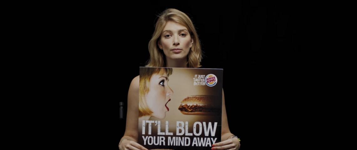 une femme tient un panneau pub sexiste dans ses mains