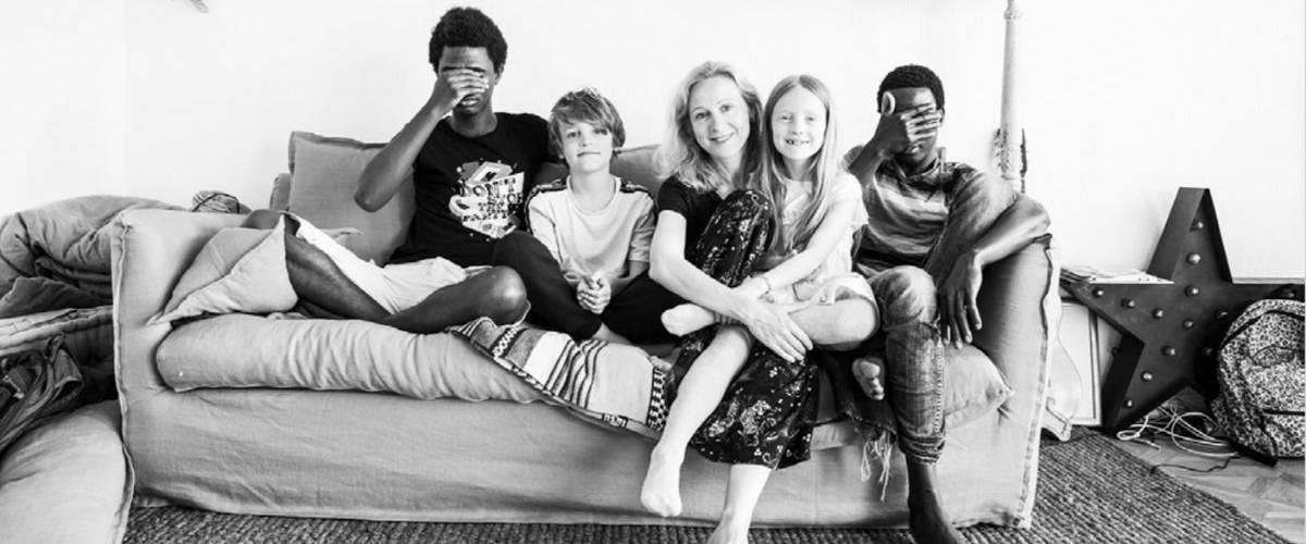 Une famille d'accueil assise sur un canapé avec leurs deux enfants immigrés