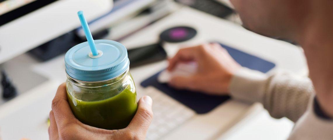 Un employé de bureau boit un smoothie vert