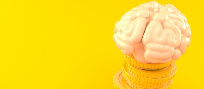 cerveau humain en or massif posé sur une pile de pièces de monnaie