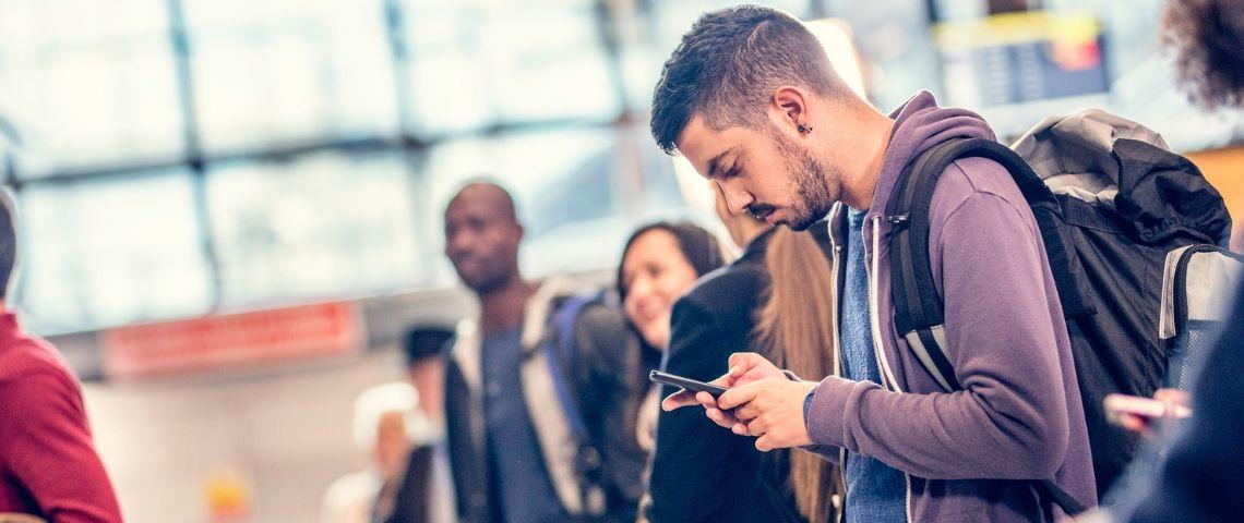 Jeune homme regarde avec anxiété son téléphone à l'aéroport