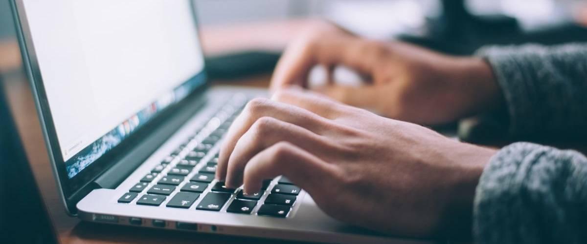 Une homme rédige sur un ordinateur portable