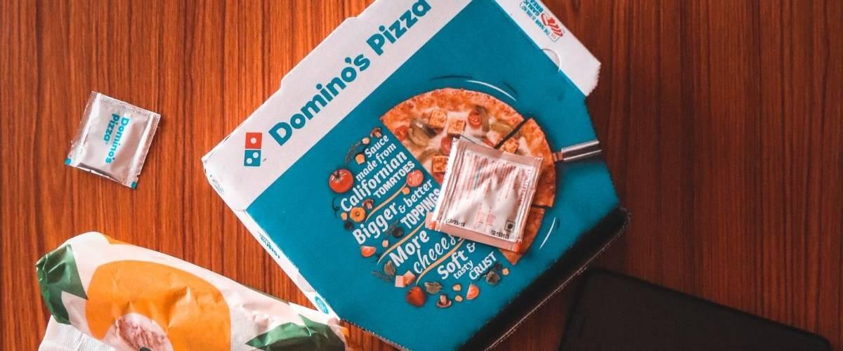 une boite pizza Domino's sur une table en bois