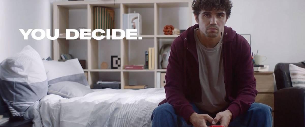 Un jeune homme assis sur son lit regarde son téléphone